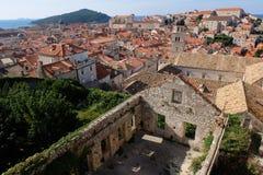 Vue au-dessus de vieux dessus de toit de ville de Dubrovnik avec des ruines en premier plan et contexte d'île de Lokrum Photos libres de droits