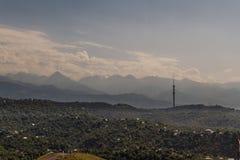 Vue au-dessus de ville vers des montagnes au-delà, avec le remorquage de communications Photos stock