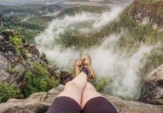 Vue au-dessus des jambes nues masculines dans la vallée brumeuse Petite pause sur la traînée photo stock