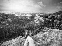 Vue au-dessus des jambes nues masculines dans la vallée brumeuse Petite pause sur la traînée images stock