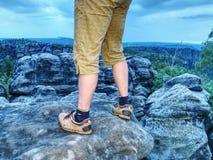 Vue au-dessus des jambes nues masculines dans la vallée brumeuse Petite pause sur la traînée photographie stock