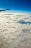 Vue au-dessus des nuages d'avion de fenêtre Images stock