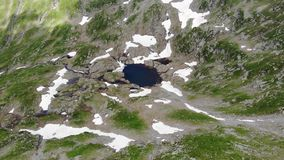 Vue au-dessus du petit lac de montagne Avec des secteurs neigeux banque de vidéos