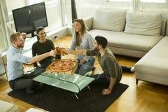 Vue au groupe d'amis mangeant de la pizza et buvant du cidre Photos libres de droits