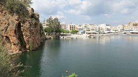 Vue au paysage urbain d'Agios Nikolaos Crete Greece Bateaux au petit voulismeni de lac de volcan et à son port Maisons traditionn banque de vidéos
