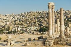 Vue aux colonnes en pierre antiques à la citadelle d'Amman avec la ville d'Amman au fond à Amman, Jordanie Photographie stock libre de droits