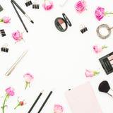 Vue avec des cosmétiques, le journal intime, le stylo, les agrafes et les roses roses sur le fond blanc Vue supérieure Configurat Photographie stock libre de droits