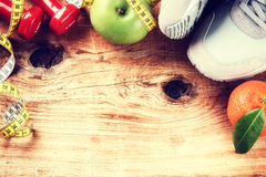 Vue avec des haltères, des espadrilles et des fruits frais Images stock