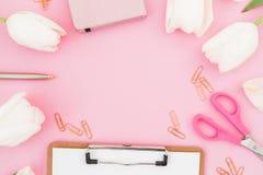 Vue avec les fleurs de tulipes, la tasse de café, le presse-papiers, les agrafes et les verres sur le fond rose Concept de Blogge Images stock
