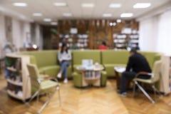 Vue brouillée d'intérieur de bibliothèque avec l'ensemble rond de sofa photos stock