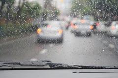 Vue brouillée de route par la fenêtre de voiture avec la goutte de pluie Images libres de droits