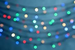 Vue brouillée des lumières de Noël sur le fond de couleur photo stock