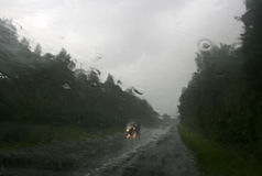 Vue brouillée : la route, la forêt et la voiture dans le versement pleuvoir photographie stock libre de droits
