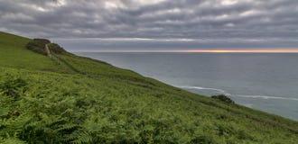 Vue côtière BRITANNIQUE de chemin, avec un ciel nuageux et un coucher du soleil mince Photographie stock