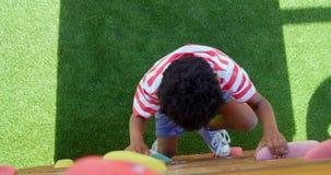 Vue courbe d'écolier d'Afro-américain jouant dans le terrain de jeu d'école un jour ensoleillé 4k clips vidéos