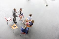 Vue courbe d'homme d'affaires parlant aux collègues au bureau pendant se réunir image stock