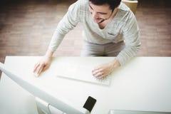 Vue courbe d'homme d'affaires travaillant sur l'ordinateur Image stock