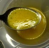 Vue courbe d'huile fraîche s'habillant avec le jus de citron sur une cuillère pour la salade Photos libres de droits