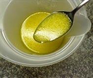 Vue courbe d'huile fraîche s'habillant avec le jus de citron sur une cuillère pour la salade Image libre de droits