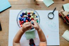 Vue courbe d'un enfant en bas âge tenant des perles au-dessus d'une cuvette photos libres de droits