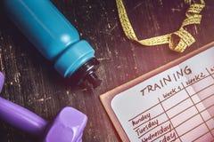 Vue courbe d'un plan de séance d'entraînement dans le carnet au bureau en bois images libres de droits