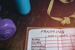 Vue courbe d'un plan de séance d'entraînement dans le carnet au bureau en bois images stock
