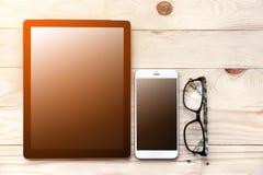 Vue courbe de bureau d'homme d'affaires avec le téléphone portable et le comprimé, s Photographie stock