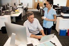 Vue courbe de collègue masculine se tenante prêt de femme d'affaires dans le bureau Images stock