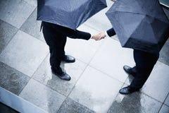 Vue courbe de deux hommes d'affaires tenant des parapluies et se serrant la main sous la pluie photos libres de droits