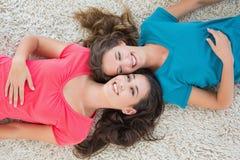 Vue courbe de deux jeunes amis féminins se trouvant sur la couverture Photographie stock