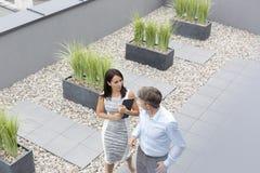 Vue courbe de femme d'affaires communiquant avec le collègue à la terrasse de bureau photo stock