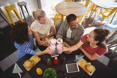 Vue courbe de jeunes amis de sourire soulevant le pain grillé tout en se reposant au café Photo stock