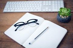 Vue courbe de journal intime avec le stylo et de lunettes par le clavier Photo stock