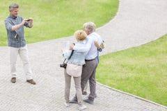 Vue courbe de l'homme photographiant des amis au parc Photographie stock libre de droits