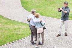 Vue courbe de l'homme photographiant des amis au parc Image stock
