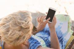 Vue courbe de la femme à l'aide du téléphone intelligent tout en se reposant sur la chaise Photo stock