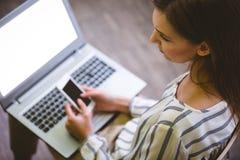Vue courbe de la femme d'affaires à l'aide du téléphone portable au-dessus de l'ordinateur portable au bureau photographie stock