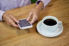 Vue courbe de la femme supérieure à l'aide du téléphone intelligent au café Images stock
