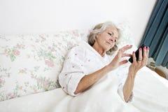 Vue courbe de la femme supérieure à l'aide du téléphone intelligent dans le lit à la maison Photos libres de droits