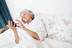 Vue courbe de la femme supérieure à l'aide du téléphone intelligent dans le lit à la maison Photographie stock libre de droits