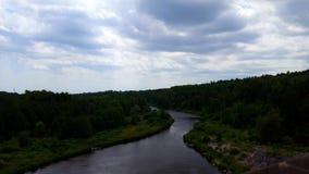 Vue courbe de la rivière débordante calme entourée par les forêts vertes luxuriantes sous le ciel nuageux clips vidéos