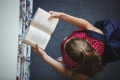 Vue courbe de livre de lecture attentif d'écolière dans la bibliothèque Photo stock