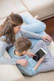 Vue courbe de mère et de fils à l'aide de la tablette sur le sofa Images stock