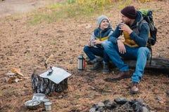 vue courbe de thé potable heureux de père et de fils de thermos images stock