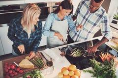 Vue courbe de trio faisant cuire un repas Images libres de droits