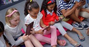 Vue courbe des écoliers de métis étudiant sur le comprimé numérique dans la bibliothèque d'école 4k banque de vidéos