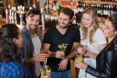 Vue courbe des amis de sourire tenant des boissons tout en se tenant ensemble Image stock
