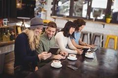 Vue courbe des amis heureux employant des technologies à la table Photographie stock