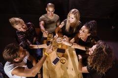 Vue courbe des amis heureux grillant à la table Photo libre de droits