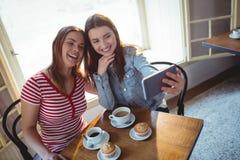 Vue courbe des amis heureux prenant le selfie au café Images libres de droits
